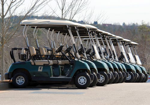 A dozen, green, single seater golf buggies in a row.